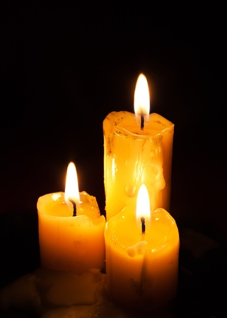 Three old white candles on black background photo