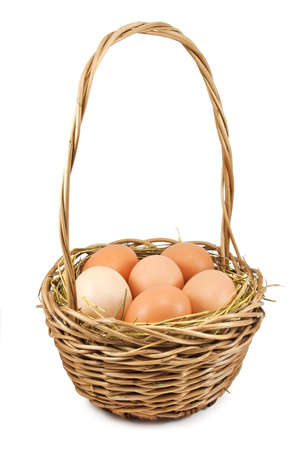 Brown eggs at hay in the basket on white photo