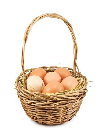Huevos de color marr�n en el heno de la cesta sobre fondo blanco Foto de archivo