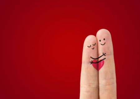 two fingers: А happy couple in love with painted smiley and hugging Stock Photo