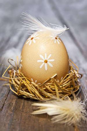 Easter egg in nest on wooden table photo