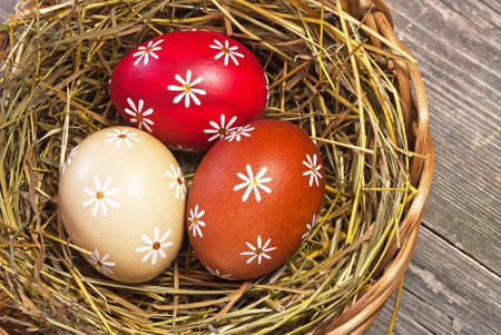Colorful easter egg in the basket on wooden table photo