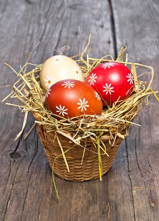 easter nest: Colorful easter egg in the basket on wooden table Stock Photo