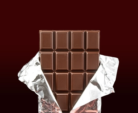 eating chocolate: chocolate bar with open cover on dark background Stock Photo