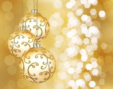 Three beautiful golden christmas balls on a golden background Stock Photo