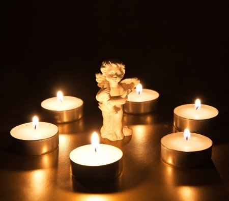 Christmas angel with candles over dark background photo