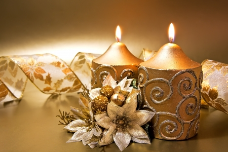 poinsettia: Christmas decoration with candles and ribbon over golden background Stock Photo