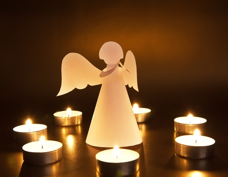holy angel: Christmas angel with candles over dark background