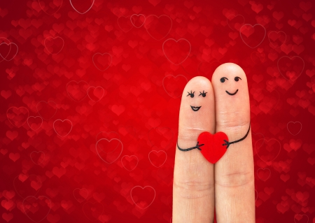 two fingers: Happy couple in love with painted smiley holding red heart