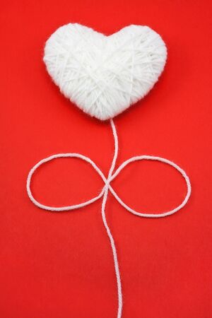 White heart shape made from wool on red background photo