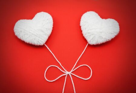string together: Two white hearts made from wool on red background Stock Photo