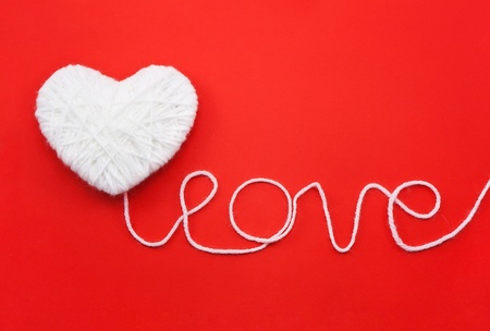 gomitoli di lana: A forma di cuore bianco di lana su sfondo rosso
