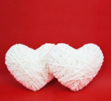 Two white hearts made from wool on red background photo