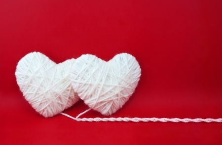 Two white hearts made from wool on red background 스톡 콘텐츠