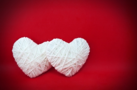 Two white hearts made from wool on red background Stock Photo - 17466827
