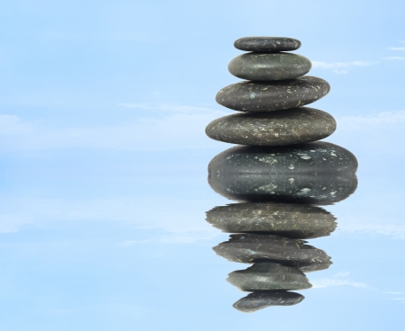 stack of balanced zen stones in water on blue sky background photo