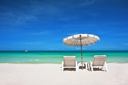 Sillas de playa con paraguas y hermosa playa de arena Foto de archivo
