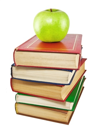 A green apple on top of a stack of old books