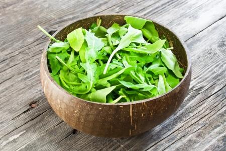 dishtowel: fresh arugula salad on wooden table Stock Photo
