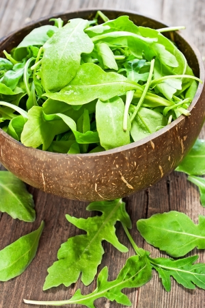 roquette: fresh arugula salad on wooden table Stock Photo