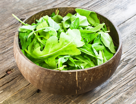 resh arugula salad on wooden table photo