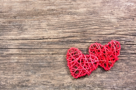 2 objects: Two red hearts on wooden background