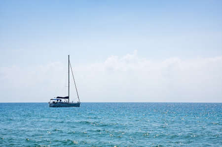 small boat: sailboat on the horizon on a sunny day