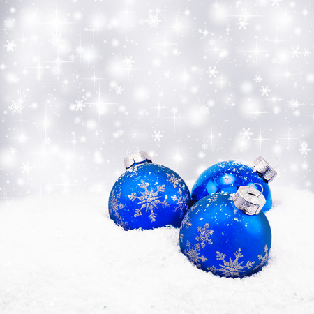 Three blue christmas balls on silver background
