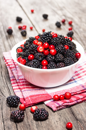 blackberries and cranberries in a bowl on wooden table photo