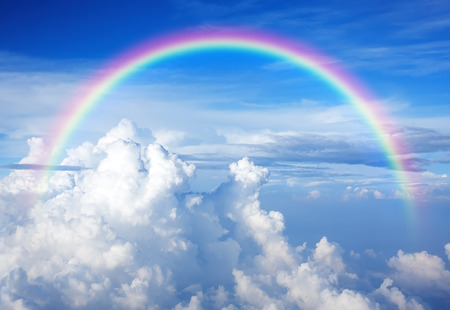 Blue sky with clouds and a rainbow