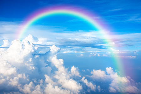 Blue sky with clouds and a rainbow photo