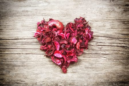 Vintage heart from red dry petals on wooden table 스톡 콘텐츠