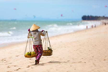 ベトナム人女性・ ビーチ Mui Ne beach で果物を販売します。ベトナム。アジア