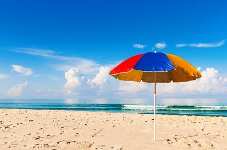 parapluie coloré et belle plage de sable