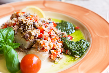 halibut: Baked halibut with vegetable garnish and couscous