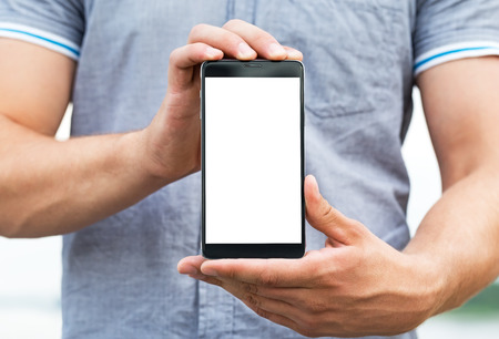 cell phone: Young man showing a mobile phone application, close up