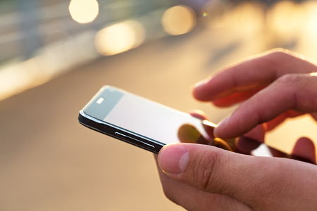 Man using his Mobile Phone outdoor, close up