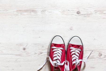 chaussure: De vieilles chaussures rouges sur fond de bois