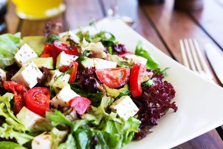 salad in plate: Ensalada mediterr�nea griega con queso feta, tomates y pimientos. Ensalada mediterr�nea. Cocina mediterr�nea. Cocina griega. Foto de archivo