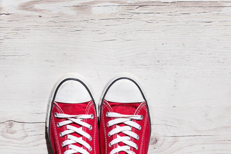 pieds sales: De vieilles chaussures rouges sur fond de bois