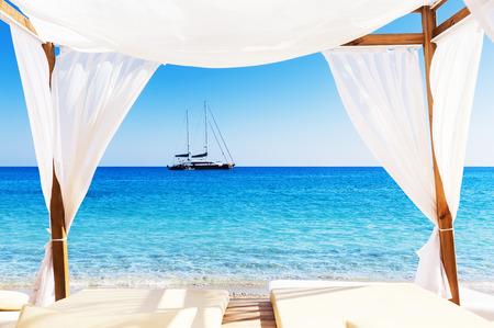 parejas romanticas: Vista de la hermosa playa a través de una cama balinesa