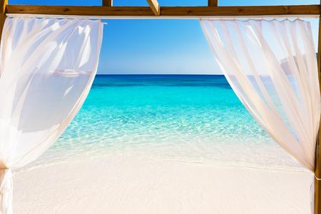 バリのベッドを通して美しいビーチの眺め 写真素材