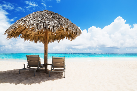 cana: Beach chairs with umbrella and beautiful sand beach in Punta Cana, Dominican Republic