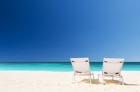 turquoise water: Beach chairs with umbrella and beautiful sand beach in Punta Cana, Dominican Republic