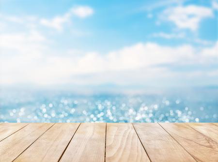 Drewniany blat na błękitne morze i biały piasek plaży w tle