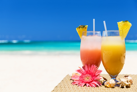 Two tropical fresh juices on white sandy beach Фото со стока