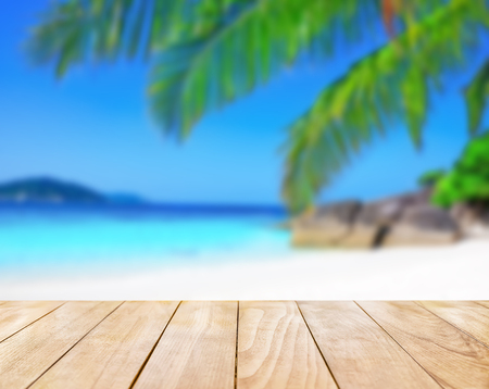 青い海と白い砂のビーチの背景に木製テーブル トップ