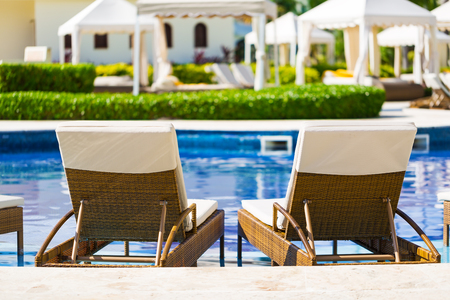 Resort swimming pool with deck chairs for relaxation