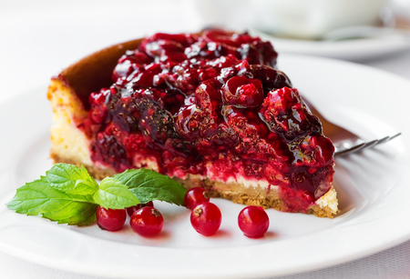 wild mint: Wild berries cake with green mint on plate with fork. Selective focus