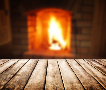 Old wooden table and blurred background of fireplace Stock Photo